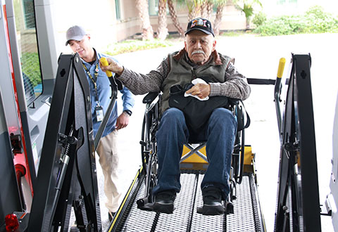 Mr. Roberto Garza-Rivera a Veteran Transportation Service driver helps disabled, Korean War Veteran Mr. Francisco Galvan prepare for his ride back home by using the electronically powered wheelchair lift located on the rear of the new VTS vehicle.
