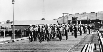 Black and white period photograph of sailors marching in formation on a dock at Port Chicago