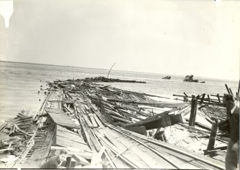 Period photograph of a dock that was ripped apart during the Port Chicago disaster. The remnants of the SS Quinault Victory appear in the background.