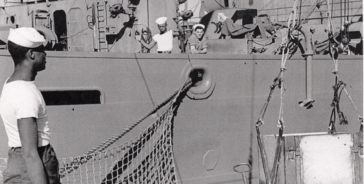 Photograph. A sailor looks onto a docked ship that is receiving supplies and munitions. Two sailors look toward the camera from the ship.