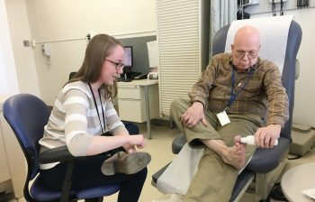 Health science specialist Tova Bergsten watches as Army Reserve Vietnam-era Veteran Stephen Fisher demonstrates a special thermometer being used in STEP UP that can help detect early-stage ulcers. (Photo by Claudie Benjamin)