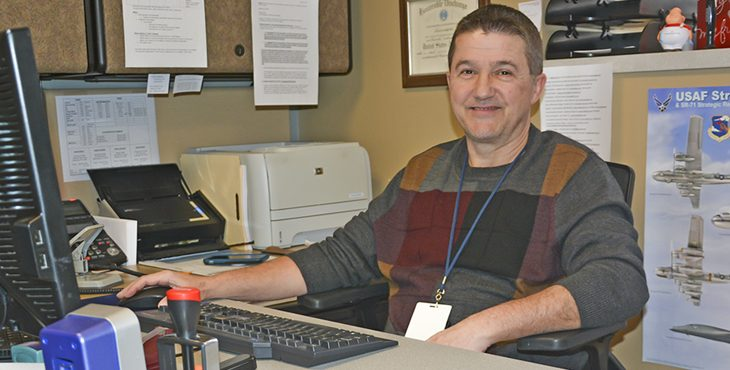 Picture of Thomas smiling, sitting at his desk