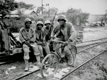 Image: Photograph of Montford Point Marines in Saipan. One is sitting on a bicycle and three sit on a rail car