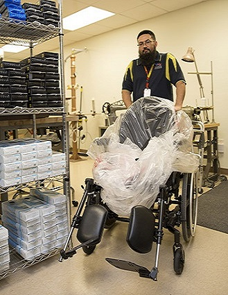 Prosthetic and Sensory Aids Service purchasing agent Carlos Treviño helps roll a new wheel chair out for a Veteran. (Photo by Luis H. Loza Gutierrez)