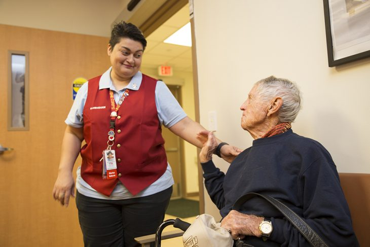 Red Coat Ambassador Lilia Garcia thanks World War II Coast Guard Veteran Jack Kelley about the local VA volunteer opportunities during for his service after escorting him to the prosthetics office located inside the VA Health Care Center at Harlingen, Texas, March 8, 2018. Red Coat Ambassadors help Veterans in many ways, which include escorting them the proper locations for their VA appointments. (U.S. Department of Veterans Affairs photo by Luis H. Loza Gutierrez)