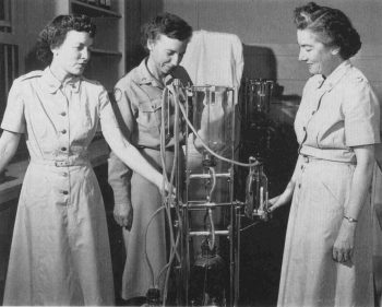 Photograph of three members of the Women's Army Corps working on a blood machine