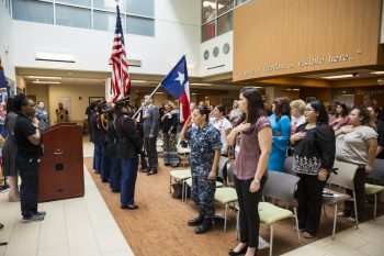 "Guests rise to their feet with render salutes and hands over their chest as the Harlingen High School All-Female Army Junior ROTC Color Guard present the colors, while the ""Star Spangled Banner"" is sung by Mrs. Rebecca Arismendi, during the VA Texas Valley Coastal Bend Health Care System's ceremony in observance of national Women's History Month, which took place March 2, 2018, at the VA Health Care Center at Harlingen, Texas."