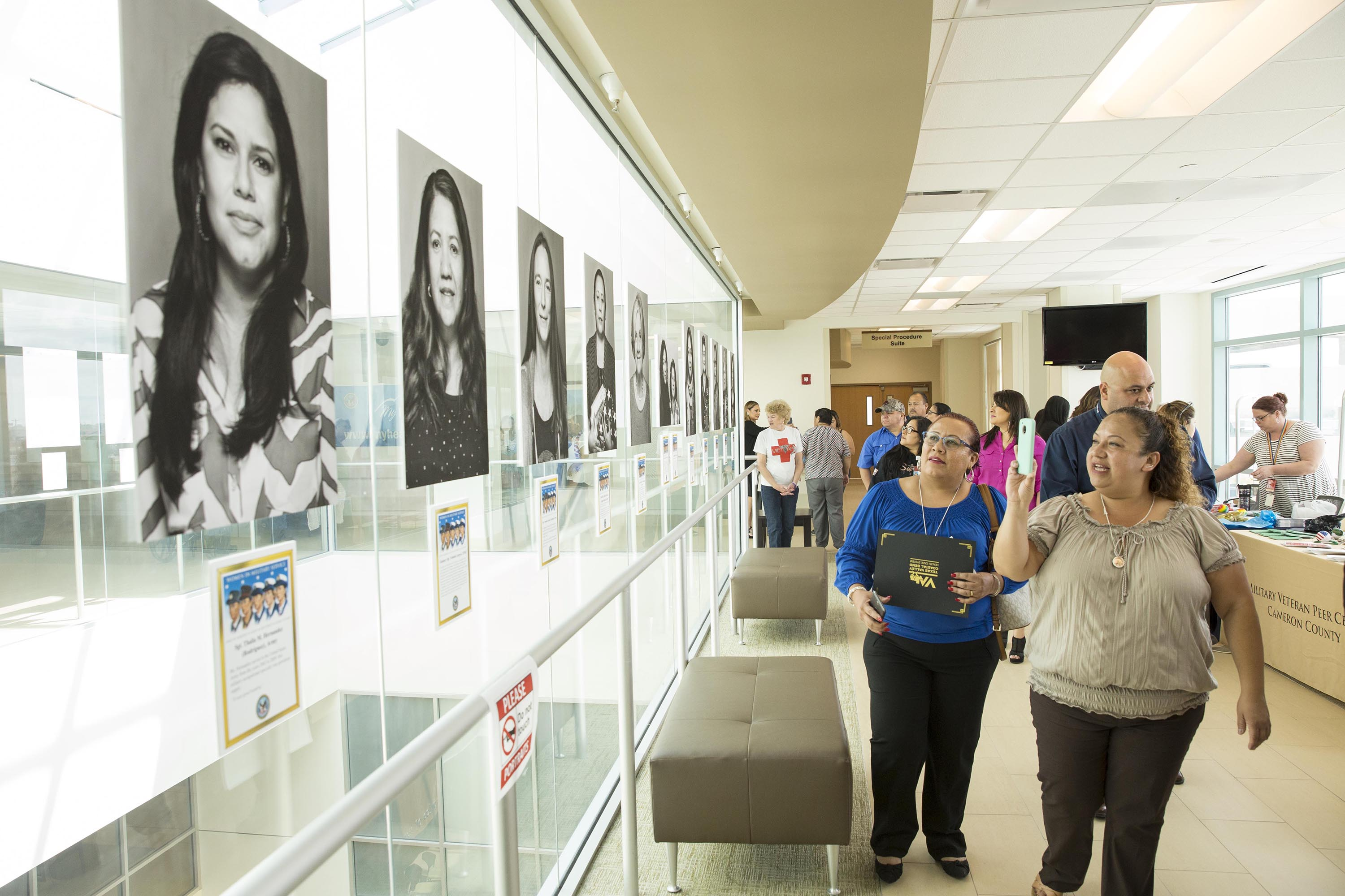 Guests tour the photo exhibit March 2, 2018, at the VA Health Care Center at Harlingen, Texas. The VA recognized Women Veterans with an exhibit of black and white portraits on the third floor featuring 29 Women Veterans from various communities. (U.S. Department of Veterans Affairs photo/Luis H. Loza Gutierrez)