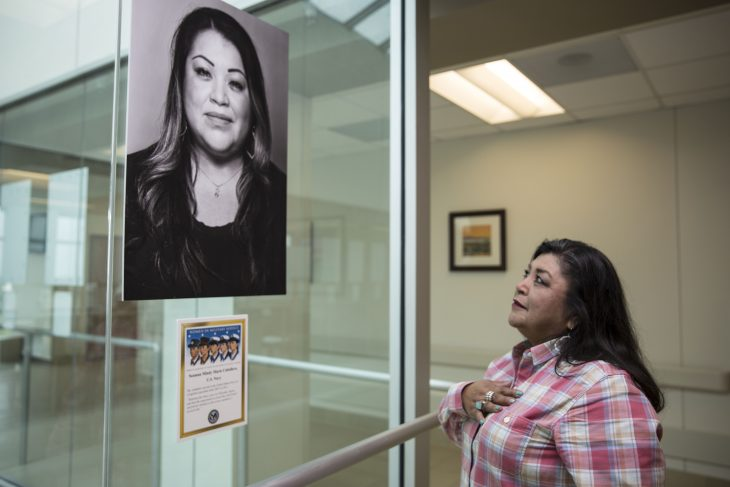 March 8, 2018, Maria Claudio Martinez places her hand over her heart as she gazes up at the portrait of her daughter Navy Veteran Navy Veteran Mindy M. Caballero, who's portrait is on display as part of the photo exhibit at the VA Health Care Center at Harlingen, Texas.