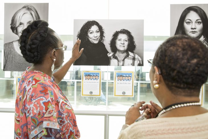 Guests admire and discuss one of the 28 portraits on display as part of the photo exhibit