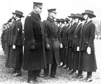 Photograph shows female Yeomen standing in formation while two male officers inspect their ranks.