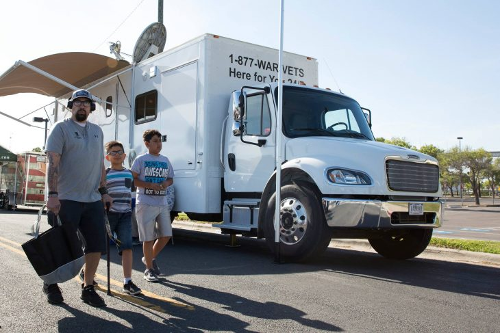 Army Veteran Jeremy Homes and his children walk past the VA Mobile Vet Center that was used as designated area to help visiting Veterans enroll into the VA.  (U.S. Department of Veterans Affairs photo by Reynaldo Leal)