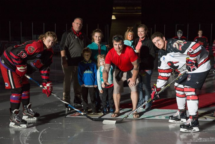 (At center) Marine Corps Veteran Brandon Bunch and his family pose for a group photo between NAHL players defenseman, number 13, Zach Herman from the Odessa Jackalopes and Corpus Christi Ice Rays forward, number 9, Angus Scott. The Bunch family were asked to participate in the puck drop as part of the activities for the opening ceremony for the North American Hockey League game. (U.S. Department of Veterans Affairs photos by Reynaldo Leal)