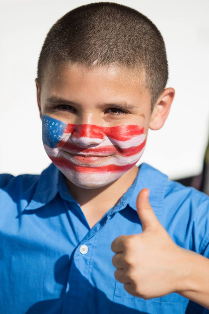 "Ismael ""Smiley"" Vela gives a thumb-up as his response to what he thought of the U.S. flag he asked an RGV Pin-Ups member to paint on his face during the 2018 Welcome Home event for Veterans. Smiley is the family dependent of Navy Veteran Christopher Martinez. (U.S. Department of Veterans Affairs photos by Reynaldo Leal)"