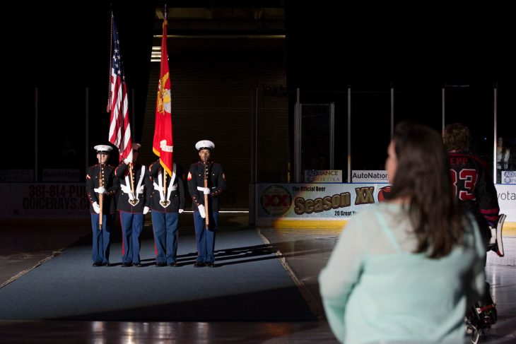 The spot light shines over the Marine Corps color guard from Charlie Company 1st Battalion 23rd Marine Regiment as they enter the ice rink for the presentation of the colors during the opening ceremony for the North American Hockey League game between the Corpus Christi Ice Rays and Odessa Jackalopes. (U.S. Department of Veterans Affairs photo by Reynaldo Leal)