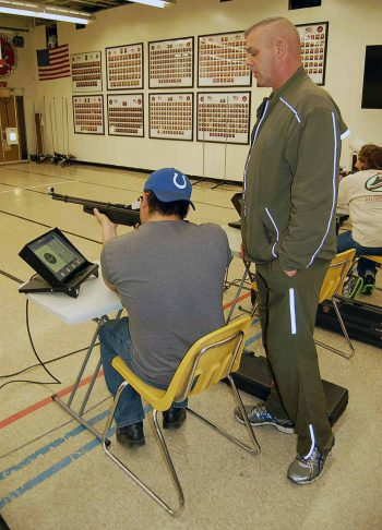 instructor stands next to man holding air rifle