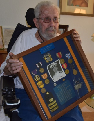 IMAGE: Jack Schwartz holds his shadow box with his medals
