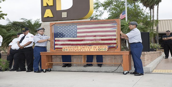 Cadets from the Mighty Hanna High School Army Junior R.O.T. C. Battalion prevent the wind from knocking down an encased U.S. flag during the remembrance ceremony .The flag behind the glass is the last U.S. flag removed from the U.S. Embassy in South Vietnam, which was the ceremonial version which stood in the U.S. Ambassador's office during the fall of Saigon in 1975. (U.S. Department of Veterans Affairs photo by Luis H. Loza Gutierrez)