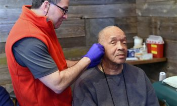 man receiving acupuncture treatment in his ear