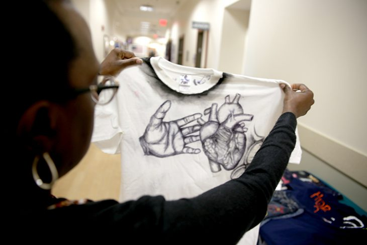 April 24, 2018 – VA psychologist Dr. Twana Cooks-Allen hold up a t-shirt decorated with ink drawings of a human hand reaching out to a heart representing the heartache of a victim of sexual assault. Some t-shirts like this one show here were decorated by victims of military sexual trauma for display on a clothesline created for the VA's observance of Sexual Assault Awareness Month. (U.S. Department of Veterans Affairs photo by Luis H. Loza Gutierrez)
