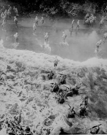Photograph of Marines assaulting the beach at Cape Gloucester through rough waters.