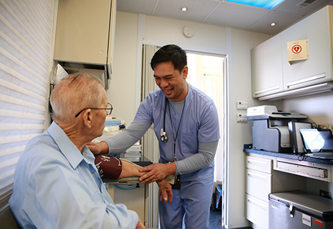 "VA registered nurse Renante ""Bobby"" Dizon smiles as he takes C.G. Powell's blood pressure reading aboard the VA Texas Valley Costal Bend Health Care System's Mobile Medical Unit (MMU), which was on site in Falfurrias, Texas, on Feb. 26, 2018."