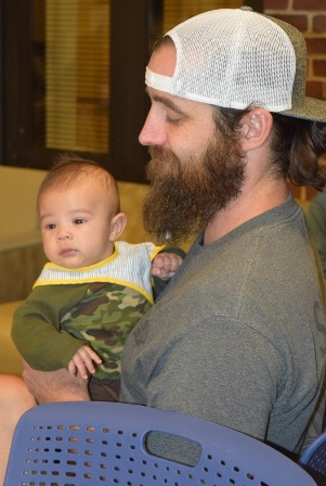 Image: Hunter Mao held by Veteran Adam Jordan, a soon to be first-time dad. Adam attends a VA group with Samey Mao, they became fast friends and Mao was happy to have him trial Hunter during the shower
