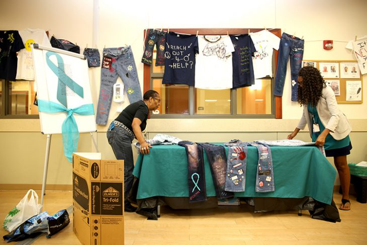 April 24, 2018 – VA peer support apprentice Karen E. Lara helps military sexual trauma coordinator Melica Wiley finish setting up a table with decorated denim jeans for a special clothesline on public display at the VA's outpatient clinic in Harlingen, Texas. The clothesline was displayed in observance of this year's Sexual Assault Awareness Month. The clothesline featured denim clothing for the first time in four-year history of the display. The denim clothing was added to the display in observance of Denim Day, which took place April 25, 2018. (U.S. Department of Veterans Affairs photo by Luis H. Loza Gutierrez)