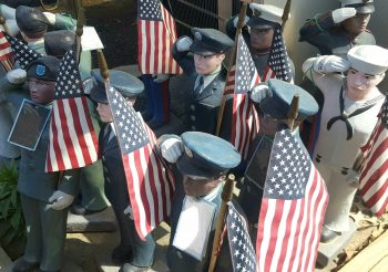 group of small painted-concrete soldier/sailor figures holding small flags