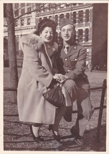 Black and withe photograph shows Harry and Edith Weber sitting on a gate in a park