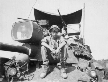 IMAGE: A young Louma sitting on a tank in Vietnam