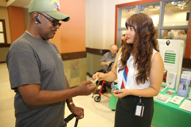 VA social worker Maribel Barcenas hands Army Veteran Fred Patton, a camouflaged, rubber bracelet with the Veterans Crisis Line number [1-800-273-8255 press 1]. Patton stopped by the information tables on display for Mental Health Awareness Month at the VA outpatient clinic in Harlingen, Texas, on May 25, 2018. Barcenas along with several VA social workers and mental health professionals hand out goodies such as stress balls and wristbands baring he Veterans Crisis Line number and information at various public outreach events throughout the year. (VA archive photo by Luis H. Loza Gutierrez)