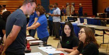 IMAGE: a Veterans talks to staff at a hiring event