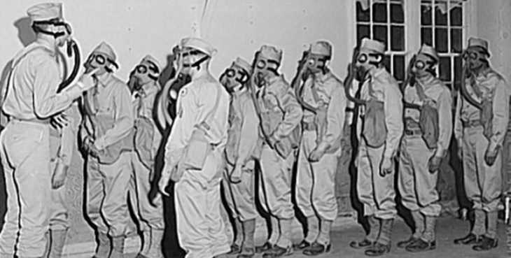 IMAGE: WWII troops in a gas Chamber with protective masks.