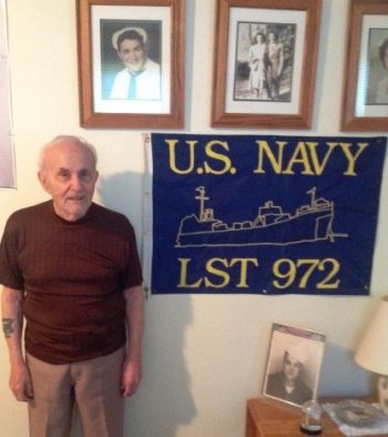 Mr. Aprea stands proudly beside some of his military memorabilia and photographs.
