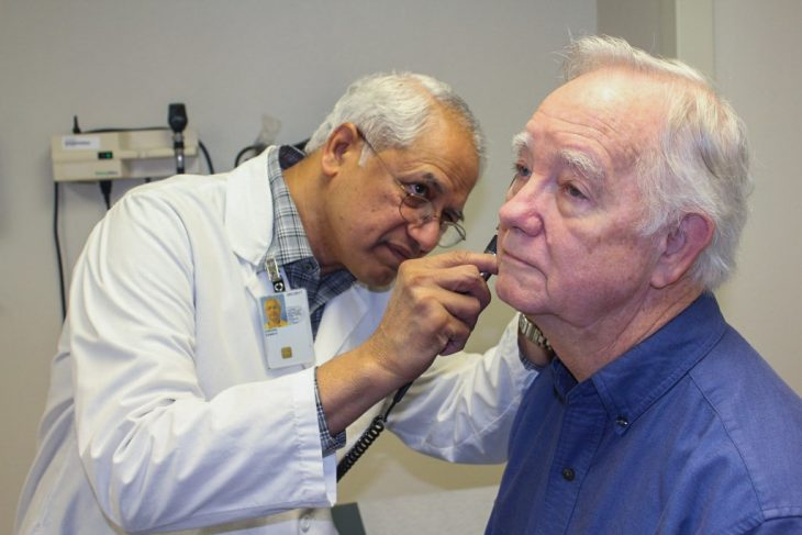 Doctor examining ear of elderly man