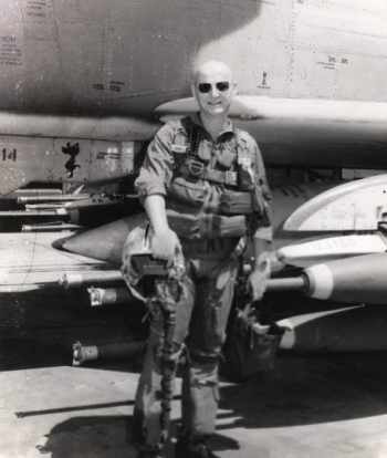 Photograph shows Andrews posing for a photograph in front of his aircraft and in his pilot uniform.