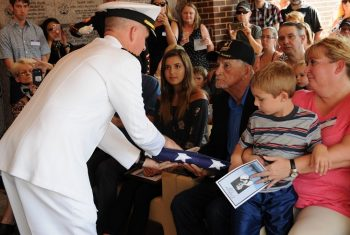 IMAGE: A sailor presents a flag to the family of Seaman 1st Class Eugene Woodrow Wicker