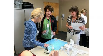 Patty Axtell, RN, and Suzanne Rainforth, LPN, practice pelvic exam supply set-up with instructor Jonna Brenton, RN, at Grand Island VAMC