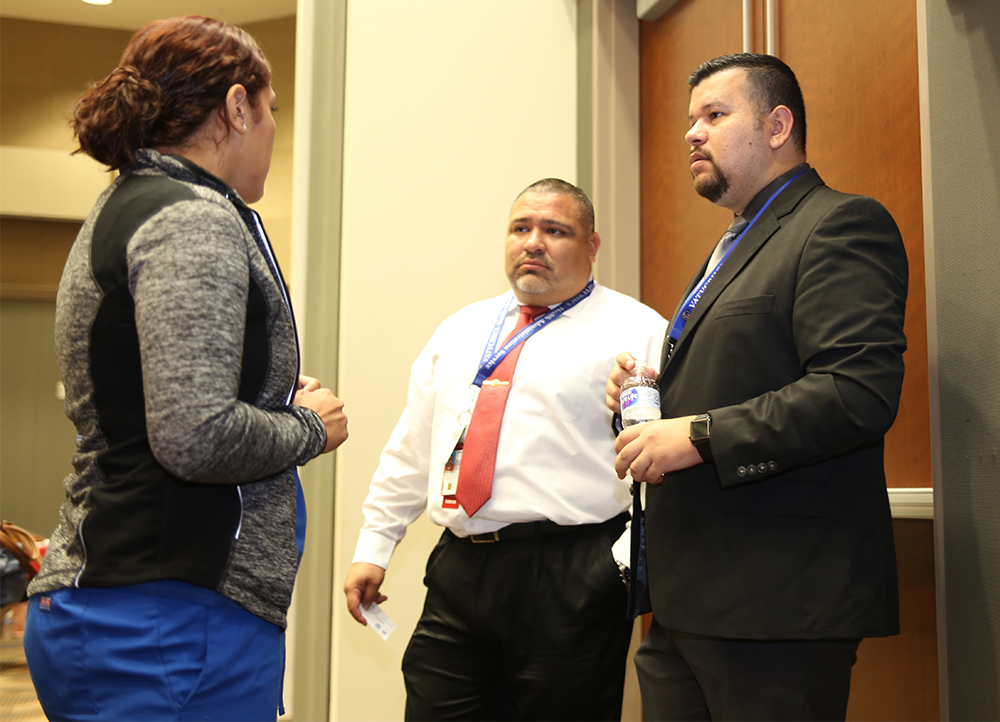 VA Texas Valley Coastal Bend Health Care System employees Timothy Rivera and Efren Cerda-Cantu talk Cynthia Carmona a dental office manager from Brownsville, Texas, who along with other dental health professionals attended the VA vendor fair held at the UTRGV Academic and Clinical Research Building in Harlingen, Texas, on August 9, 2018. (U.S. Department of Veterans Affairs photo by Luis H. Loza Gutierrez)