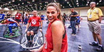Woman smiling, sitting in a wheelchair on a basketball court with others in wheelchairs around her