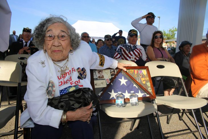 Velia Alaniz leans forward while holding on to the shadow box with the U.S. flag given to her and her husband after her son Paul Gilbert Alaniz Jr. was killed in action during the Vietnam War. Mrs. Alaniz and her husband Paul Sr. (a World War II Navy Veteran) attended the rededication ceremony of the VA outpatient clinic in Corpus Christi, Texas, held on April 27, 2018.