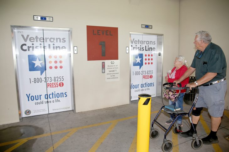 Navy Veteran Richard W. Noyes and his wife Mary notice the newly decorated elevator doors with the Veterans Crisis Line logo and number as they make their way back to their vehicle after visiting the VA Health Care Center at Harlingen, Texas, on September 11, 2018. (U.S. Department of Veterans Affairs photo by Luis H. Loza Gutierrez).