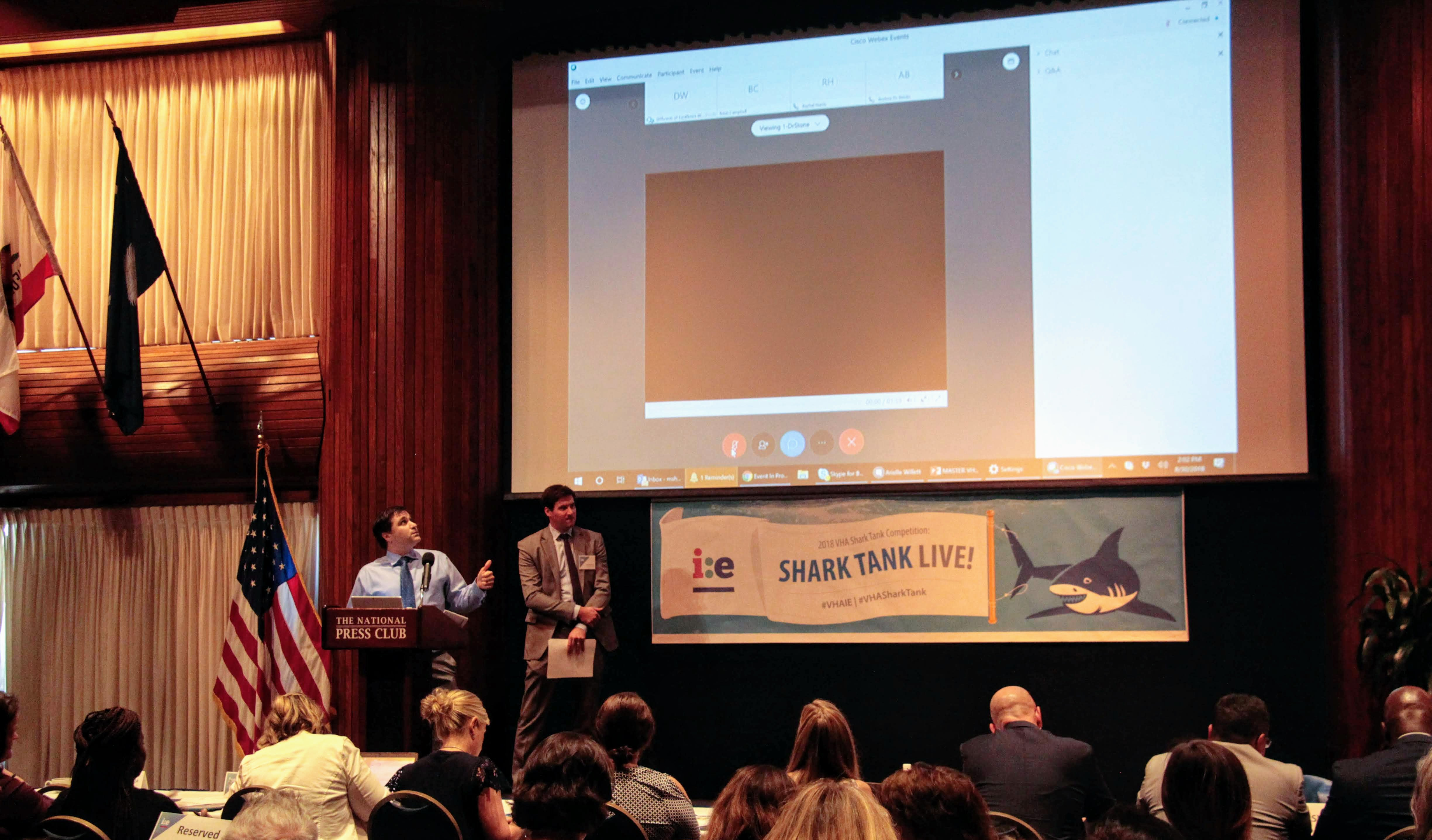 Men stand on a stage with a VHA Shark Tank banner