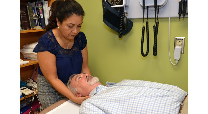 A woman performs physical therapy on a man lying down