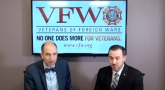 Two men looking at a camera with a TV Screen on the wall in the background. Text reads: VFW - Veterans of Foreign Wars - NO ONE DOES MORE FOR VETERANS. - www.vfw.org