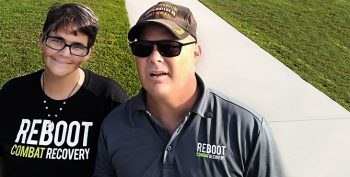 "Picture shows two Veterans wearing ""REBOOT COMBAT RECOVERY"" apparel, looking at the camera with green grass and a sidewalk behind them."