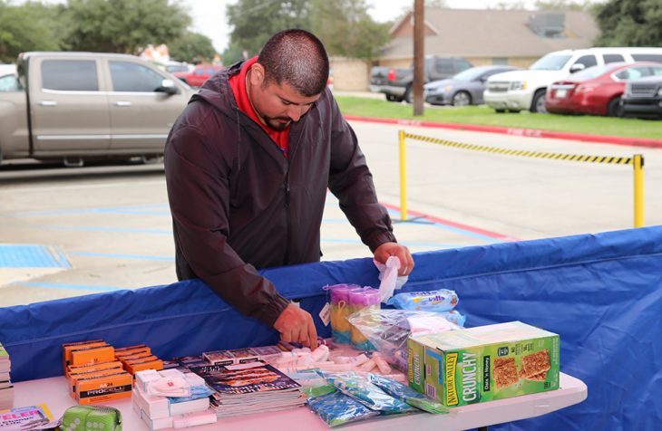 Laredo Vet Center counselor, Tobert Garcia carefully arranges some personal hygiene items donated during the Boots & Badges care package drive held October 26, 2018, at Vet Center in Laredo, Texas. (U.S. Department of Veterans Affairs photo by Luis H. Loza Gutierrez)