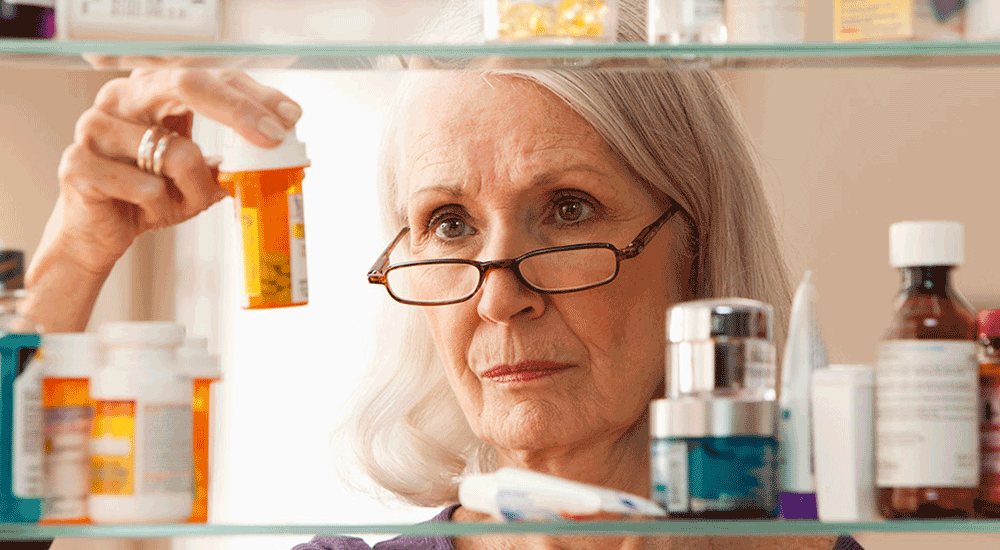 Elderly woman look at her medication in the medicine cabinet