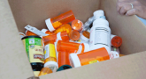 Cardboard box full of medication bottles of different sizes and shapes